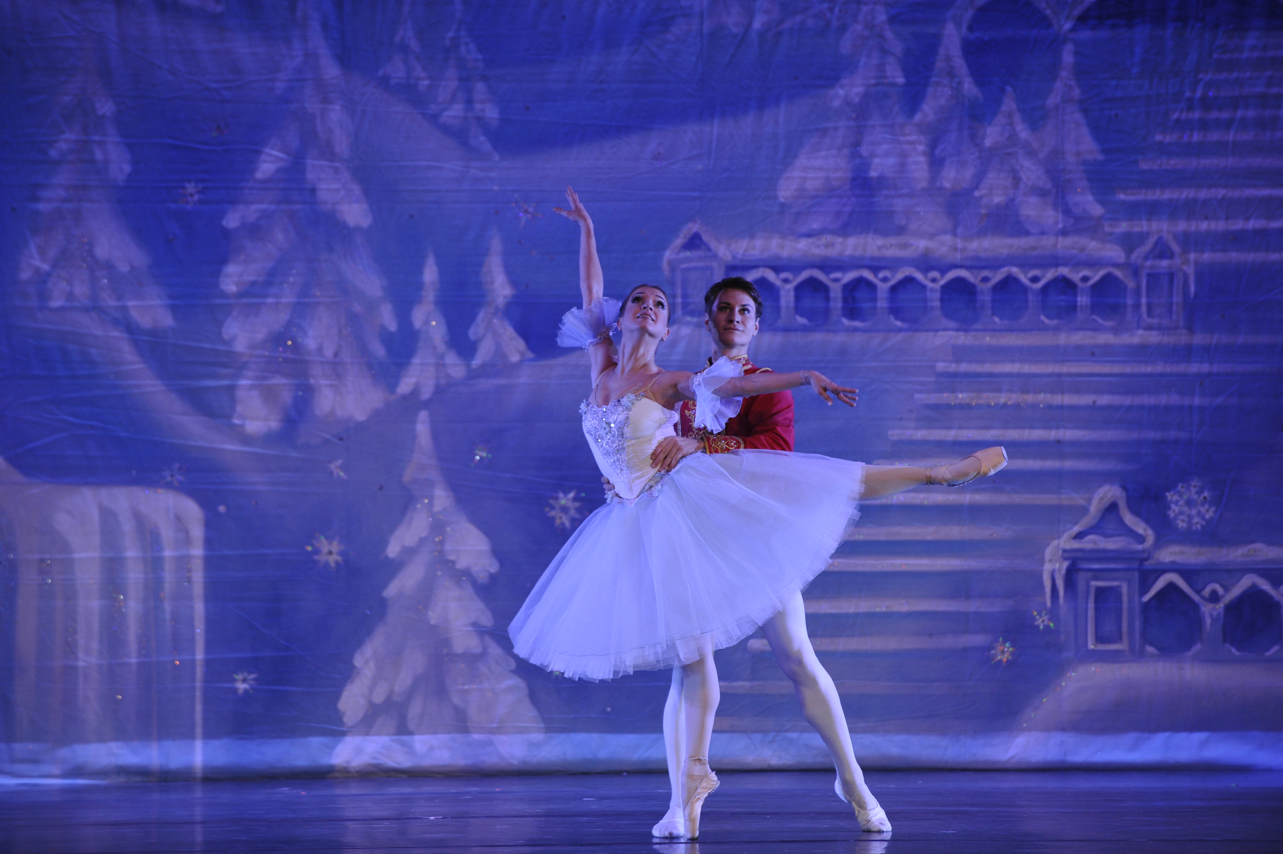 Masha in arabesque on pointe with leg extended up behind her. Her Nutcracker Prince holds her at the waist.