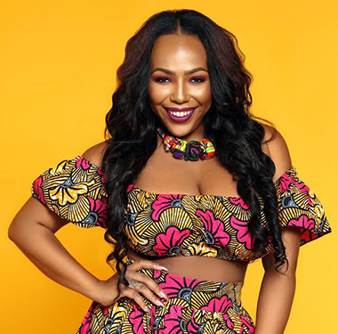 Archel Bernards is wearking one of her designs. A crop top with off the shoulder sleeves and a skirt in a pink and yellow print with a matching fabric bead necklace. She stands in front of a vibrant yellow background.