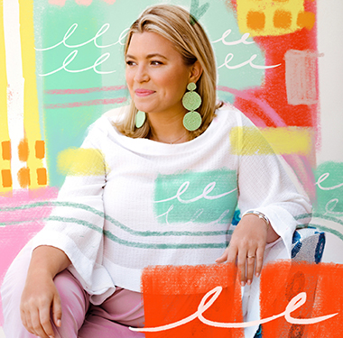Megan Fechter is wearing large green dangley earrings with a flowing white top and pink pants. There are painterly brushstrokes and designs over the background of the image.