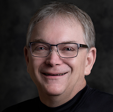 Michael Boatright wears black wireframe glasses with a black top.