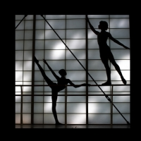 A male and female dancers are silhouetted against a backlit studio wall. The female is on the ground in arabesque en l'air and the man stands posed atop the barre in arabesque en terre.