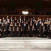 50 men and women stand in three rows on risers so they are all visible. The men wear black suits and the women wear long black dresses. Behind and above them is visible a large sheet of music which seems to be for the organist.
