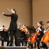 A woman stands on stage on a conductor's platform. She is wearing a black pants suit, her back is towards us, her arms are raised in front of her with a baton in her right hand. She is looking to her left. Visible to one side are several musicians playing cellos and violins.