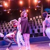 Four women are dancing on a stage, empty theater chairs visible behind them. They are in various stages of jumping, running, reaching, and bending. There is a purple light cast over them.