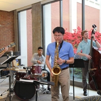In a sunny room with floor to ceiling windows along one side, four musicians are playing electric guitar, drums, saxophone, and upright bass.