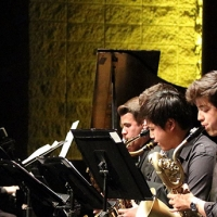 Four musicians are seated, playing saxophones and leaning towards the music stands in front of them. Facing them we can see the pianist in profile. Behind them is a brick wall illuminated in a fluorescent yellow.