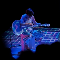 Against a black background, a woman in a silver jumpsuit sits on a chair playing a white guitar. Digital patterns in blue, purple and white are projected on her, the guitar, and the floor around her.