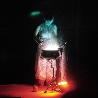Kaki King in a silver jumpsuit, standing at a single drum with multi colored lights shining up