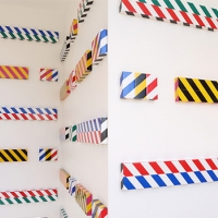 Three white walls, at 90 degree angles to each other, are hung with more than 30 different flat, rectangular canvas each covered in different combinations of industrial safety tape.