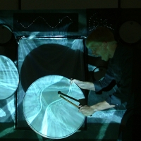 A projection of watery blue patterns of light are cast on two drum heads, each being held vertically and struck with a drumstick.