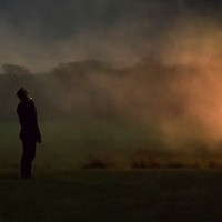 A lone, shadowy figure watches as a fire casts the countryside in an orange glow. Photo by Cig Harvey of Jackson Fine Art.