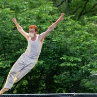 A male dancer, dressed in a beige tank top and pants and face mask, is airborne, his feet above the fence line behind him and his arms outstretched above him, silhouetted against green, leafy trees.