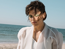 A woman standing on the beach, seen from the chest up, with sand and ocean visible behind her. She is wearing all white, her eyes closed, her hair blowing in the breeze, a bright light reflected on one side of her face.