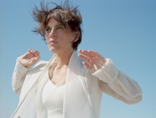 Woman in white suit faces the camera against a clear blue sky. The wind is blowing through her short brown hair.