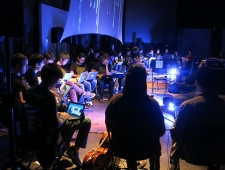 In a darkened room, casually dressed young men and women sit in a semicircle with laptop computers on their laps, intently looking at their screens. The glow from their screens illuminates their faces.