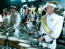 members of the Georgia Tech Yellow Jacket Marching Band, wearing white jackets with gold sashes and the gold GT insignia