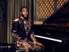 Michael Mwenso wears a velvet brown floral suit. He sits at an open grand piano, hands on his knees, while he looks straight at the camera.