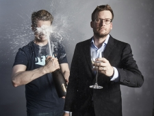 Dear Hank and John: Minotour 2020. A man in a black tshirt holds a bottle of champagne which is squirting upwards directly in his face; another man in a dark suit is facing the camera holding a glass of champagne