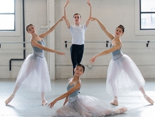 Four dancers are posed as a classical quartet. The three women wear pale blue leotards with gauzy white skirts. The man wears a white T shirt and black tights.