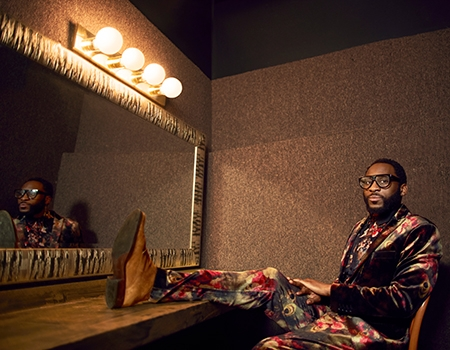 Mwenso wears black frame classes and and a velvet floral suit. He sits in a dressing room in front of a mirror with one leg propped up on the table, while he looks straight at the camera.
