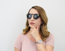 woman wearing dark sunglasses, her hand on her chin, looking off camera