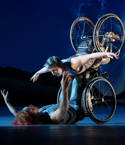 Dancers Alice Sheppard and Laurel Lawson, Alice facing upwards on her back with wheels on the ground, Laurel balanced on her stomach on Alice's legs, facing Alice, with Laurel's legs and wheels in the air behind her. Photo by Jay Newman