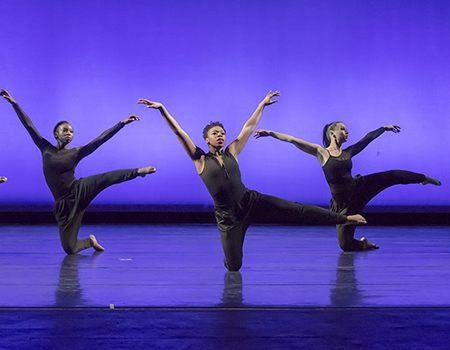 Three female dancers, bare feet, are dressed in black leotards with black pants. They balance on one knee on the ground, while the other leg and arms are outstretched. A vivid purple background is behind them.