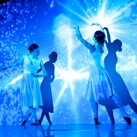 Two dancers washed in blue light with twinkling star projections.