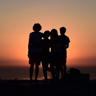 Photo of four youths in silhouette as the look out at the ocean and an orange sunset.