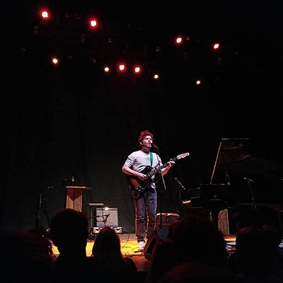 Gabriel Kahane with guitar at a microphone in performance in London.