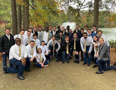 Outside on the grass, a lake and fountain behind them, are a group of 20 people, primarily men, wearing white shirts, gold ties, black pants and some also with jackets. Their hands are on their knees as they lean forward, smiling.