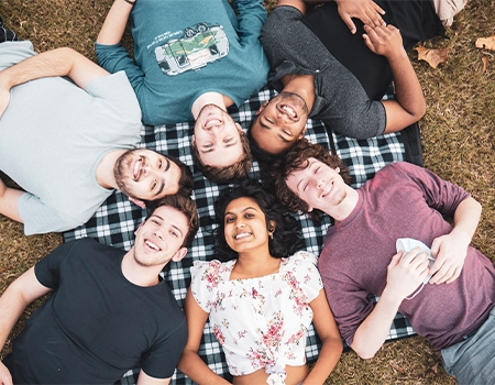 five young men and one woman are lying on the ground, face up, their heads next to eachother in a pinwheel formation.