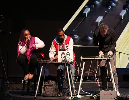 Three people on stage.  The woman holds a microphone, the two men are each working with computers and devices on a table in front of them.  A projected image of one of the men, wearing a red and white letter jacket, takes up the space behind them.