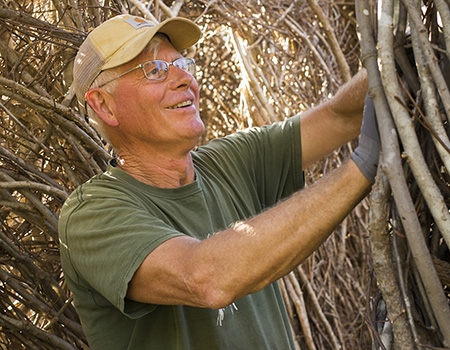Patrick Dougherty wears a beige baseball cap and green t-shirt. He is standing in one of his installations, weaving a sapling into the structure.