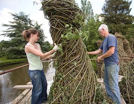 A woman and a man are outside, dressed in warm-weather work clothes. They are working with branches and saplings, adding them to a 10-foot high sculptural installation made entirely of natural materials.