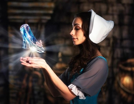 A woman with a white bonnet and blue dress and long dark hair is standing in profile. Her hands are cupped before her, a pair of glass slippers floating in the air above them.