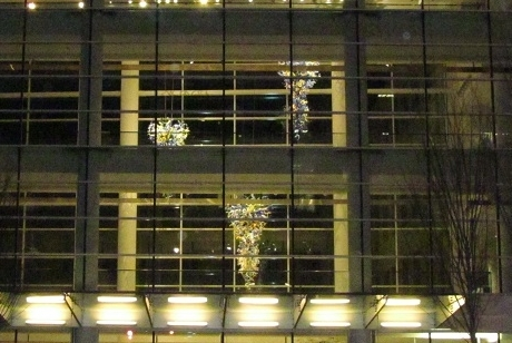 glass chandeliers seen through the three-story lobby glass windows of the Scheller College of Business
