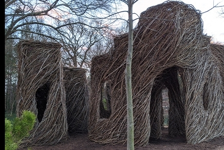 Thin saplings and branches have been woven together in the shape of cube-like buildings with arched doors and windows.