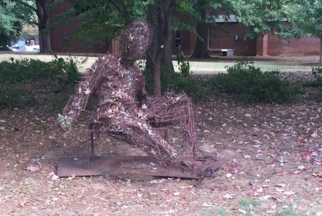 metal pieces that look like twigs, combined and shaped to look like a reclining figure