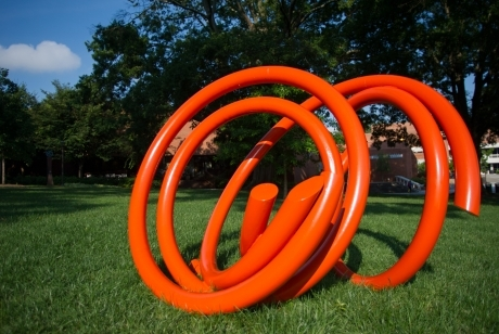 bright orange steel tubing in a twisted circular pattern on its side in the grass