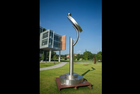 Steel pole on a multi-layered circular steel base with a mirror-like protrusion on top
