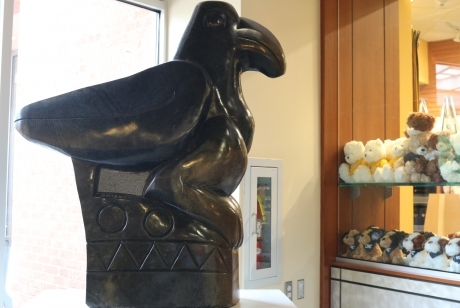 smooth black Springstone Serpentine sculpted in shape of a bird perched on a pedestal inscribed with geometric shapes