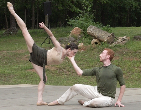The setting is an outdoors, the woods and grass surrounding a low stage. A male dancer sits, one hand touching the ground, the other gently cupping the female dancer's face. She is posed in a deep arabesque towards the man, her face in his hand and her upper arm and leg extended skyward.