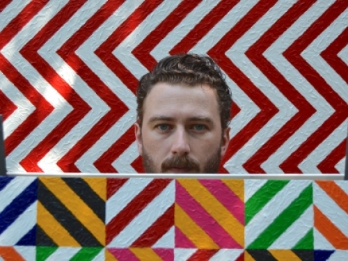 A man's head, visible from the mouth upward, is visible. He has brown, wavy hair and a close cropped beard and mustache. Behind and below him are consecutive squares each with zig zag lines of bright colors.