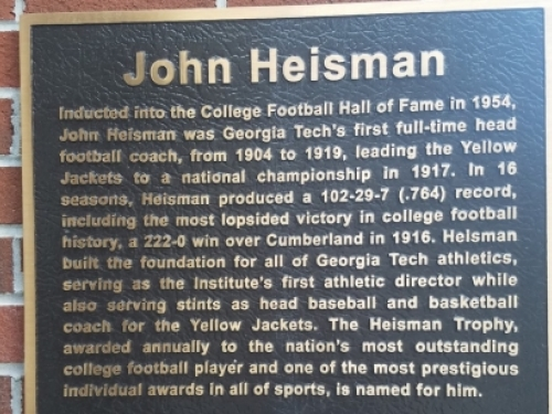 Plaque reading: Inducted into the College Football Hall of Fame in 1954, John Heisman was Georgia Tech's first full-time head football coach, from 1904 to 1919, leading the Yellow Jackets to a national championship in 1917.  In 16 seasons, Heisman produced a 102-29-7 (.764) record, including the most lopsided victory in college football history, a 222-0 win over Cumberland in 1916.  Heisman built the foundation for all of Georgia Tech athletics, serving as the Institute's first athletic director...