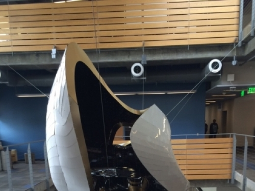 white aluminum amorphous shape with openings, suspended in the atrium of the Clough Undergraduate Learning Commons