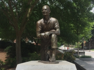 Figure of Bobby Dodd kneeling on one knee, holding a football in his left hand resting on his left knee
