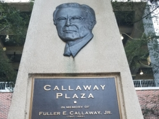Bas relief of the face of Fuller E. Callaway, Jr. on a cement tower, above a plaque recounting his devotion and dedication to Georgia Tech