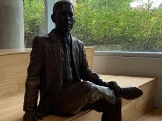 Bronze figure of Ronald L. Yancey, the first African American graduate of Georgia Tech, seated on the wide bench steps of Clough Undergraduate Learning Commons, his right leg loosely crossed with his right ankle resting on his left knee