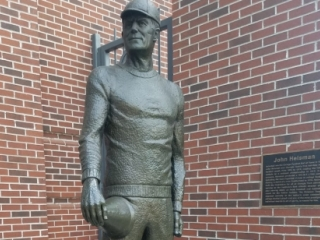 Standing figure of John Heisman, his right hand holding a bullhorn resting on his right thigh.